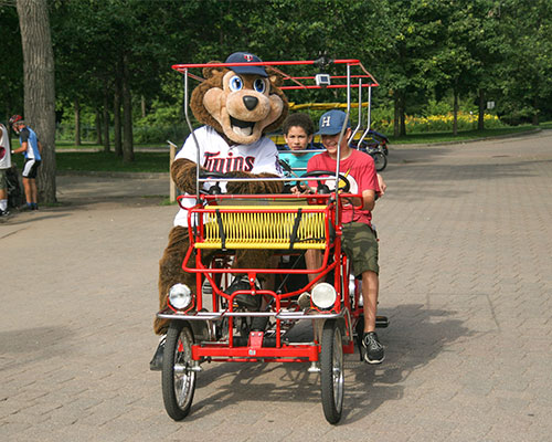 Kids riding in a surry bike with T.C. Bear
